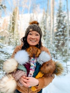 Chereen Leong Schwarz who is the owner, maker, and designer of Smeeny Beanie Knits holding beanies